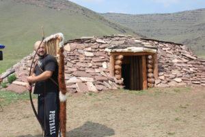 Участник экскурсии примеряет оружие воинов таштыкской культуры